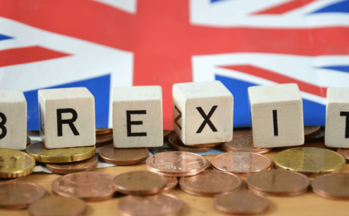 Union Jack flag and a row of Euro coins separated by a line of cubes spelling out BREXIT