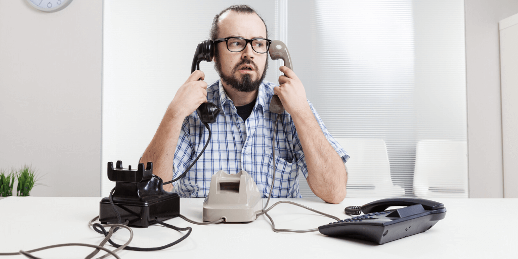 Office worker juggling several phones he looks stressed out