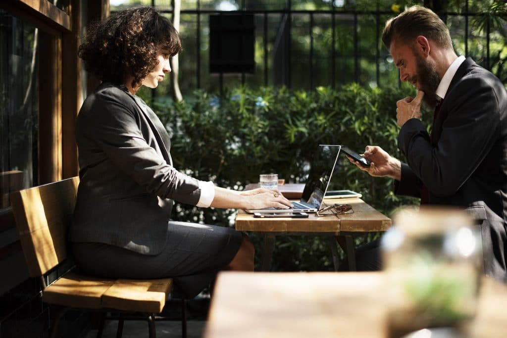 A business man and woman working at a laptop, outside on a sunny day