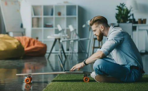 A man using a laptop perched on a skateboard in a light airy apartment. It looks like he is apply for a new job in Summer