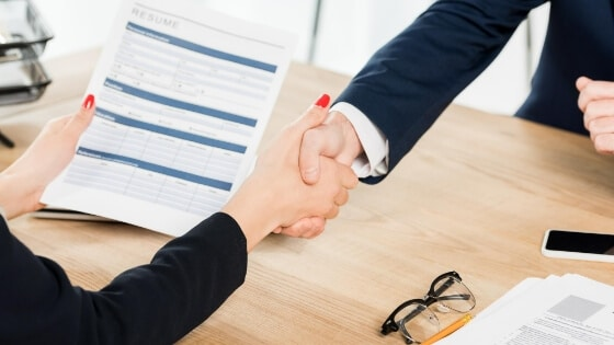 Shaking hands across a table. Doesn't it look easy? If only it was, then recruiters could certainly be accused of charging ridiculous fees