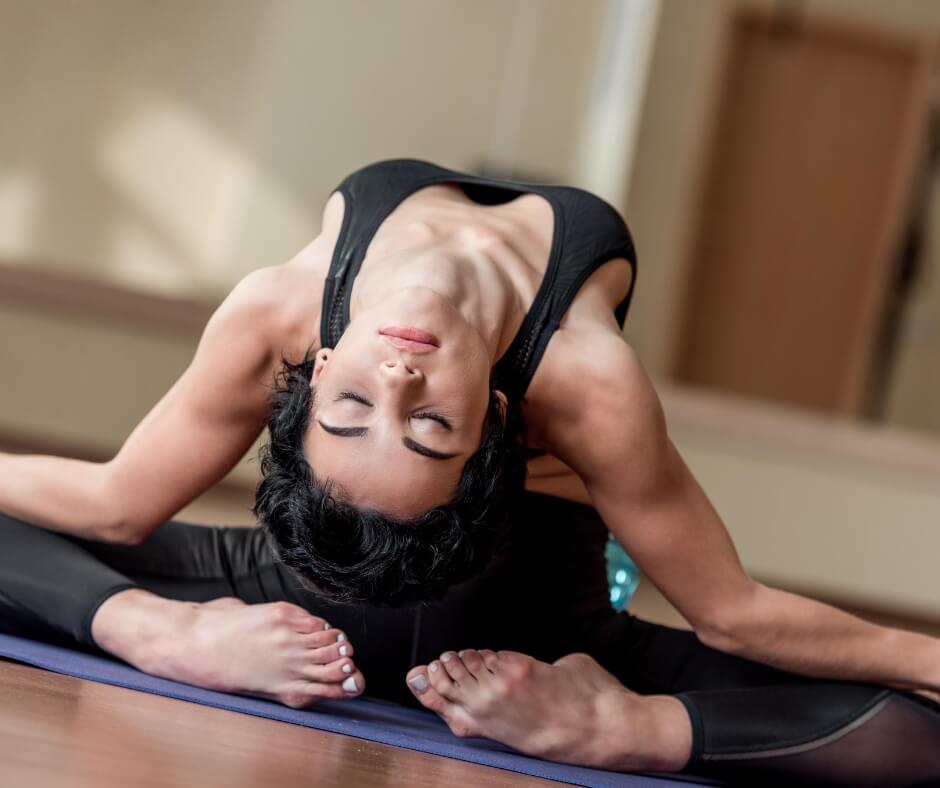 This lady is demonstrating her extreme flexibility in an advanced yoga position