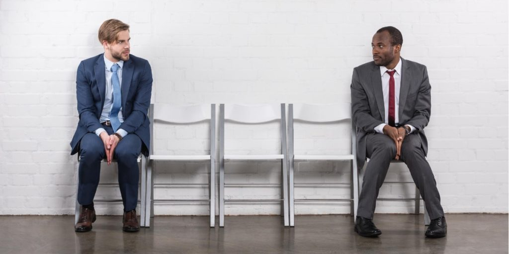 two men awaiting feedback as the interviewers debate whether they should hire a relocator