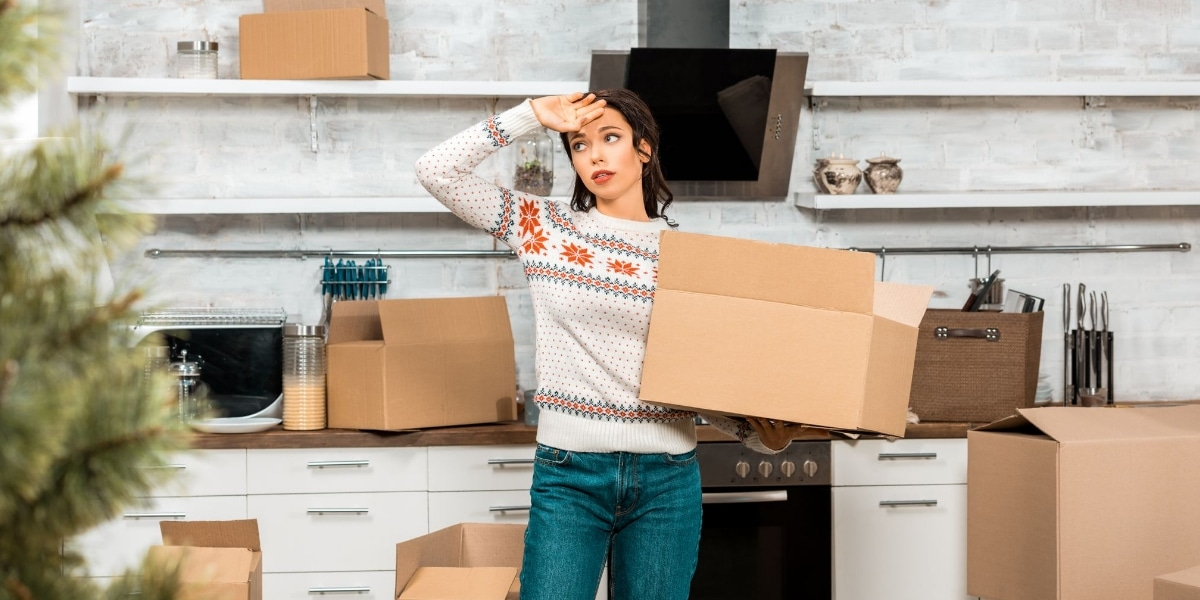 Lady looking worried after packing her stuff for her relocation up North