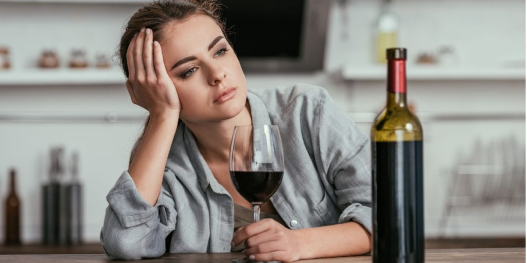 the picture shows a lady looking sad with a glass of wine.
