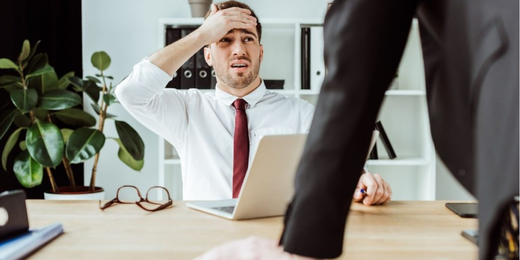 Employer covering his face looking very worried about the prospect of Blue Monday