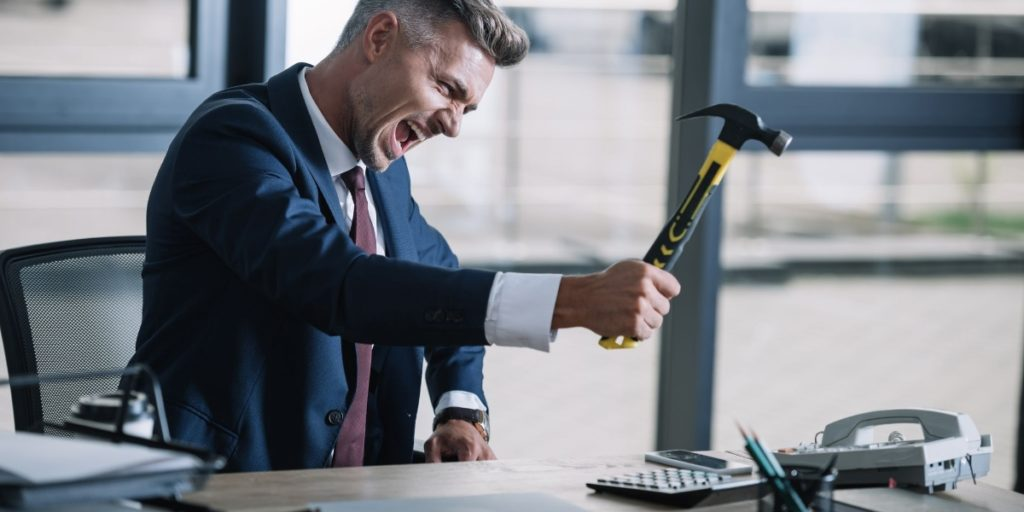 Gentleman overcoming his phone phobia by smashing it with a hammer