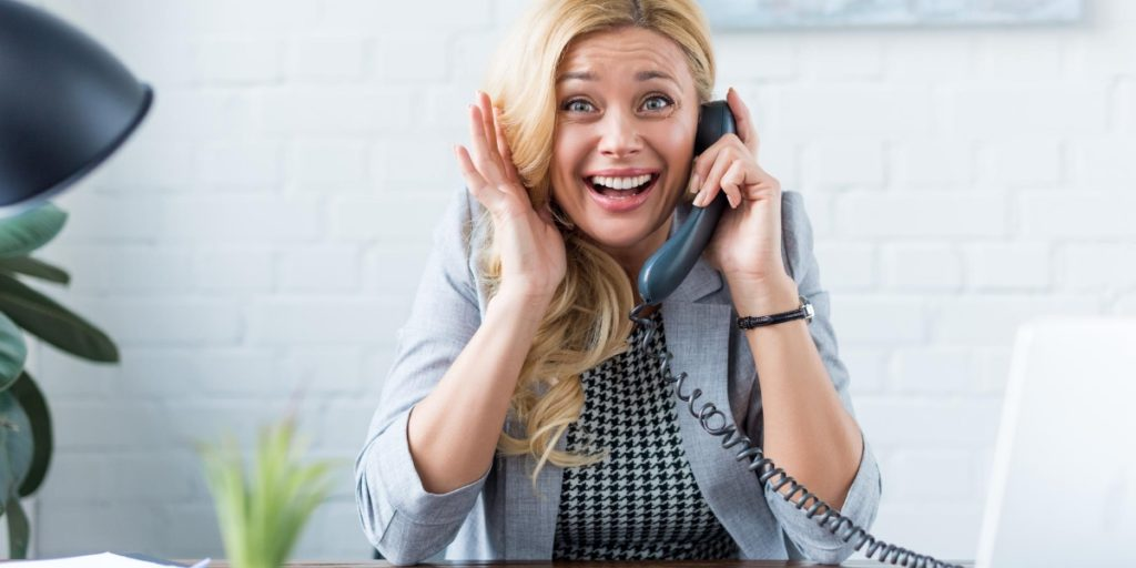 Woman pulling an uncomfortable face as she fears talking on the phone at work