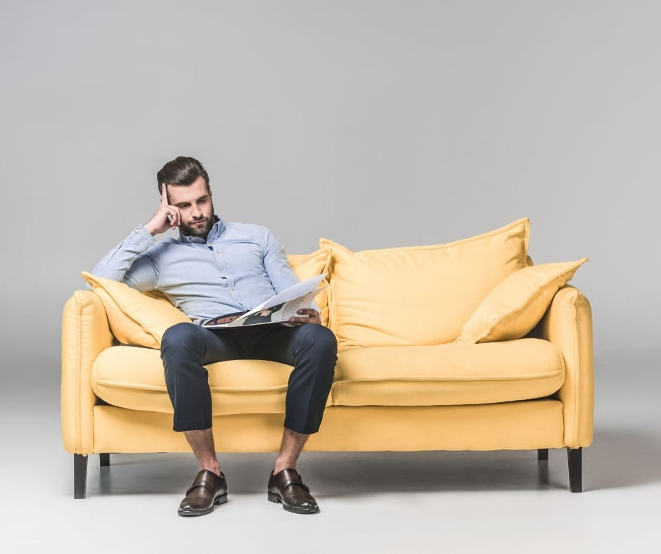 Man sitting on a sofa looking thoughtful. Is relocating to Manchester from London the right decision?