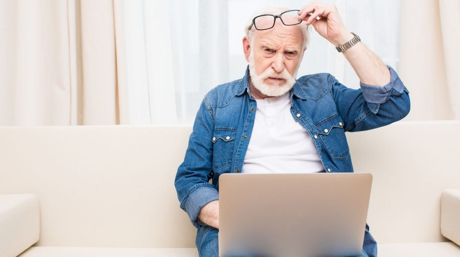 Elderly gentleman with a laptop in his lap looking perplexed