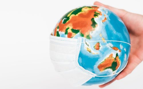 A hand holding a globe wearing a surgical mask