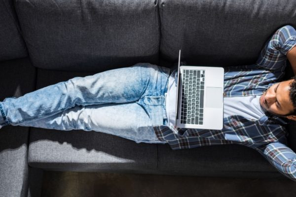 Man relaxing on the sofa with his laptop