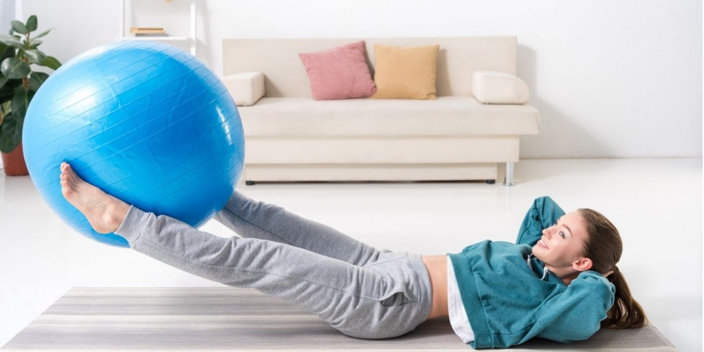 A lady working out at home with an exercise ball