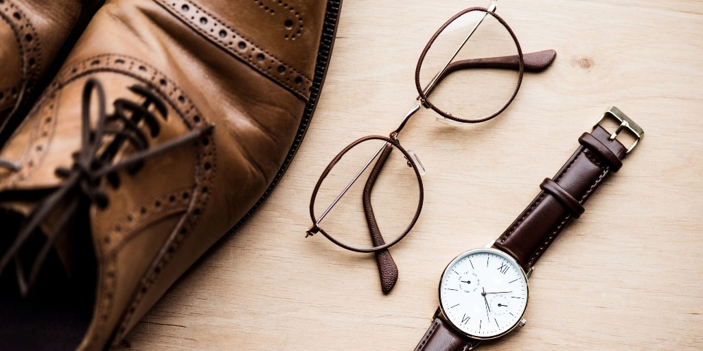Brown leather brogue shoes, a pair of glasses and a wristwatch. Wearing accessories are just one example of how to be productive when you work from home