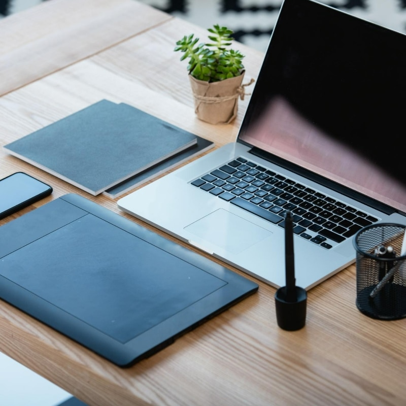 Desk furnished with a laptop, smartphone and graphics tablet. Exactly the kind of technology that a graphic designer might need to work from home