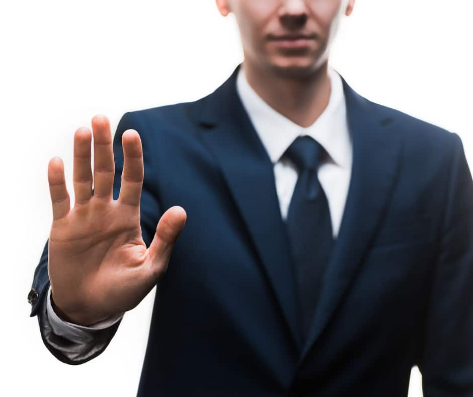 Man in a suit holding his hand up as if to refuse a request
