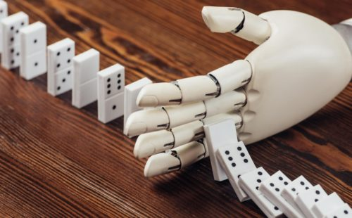 A robot hand stops a sequence of dominoes falling down