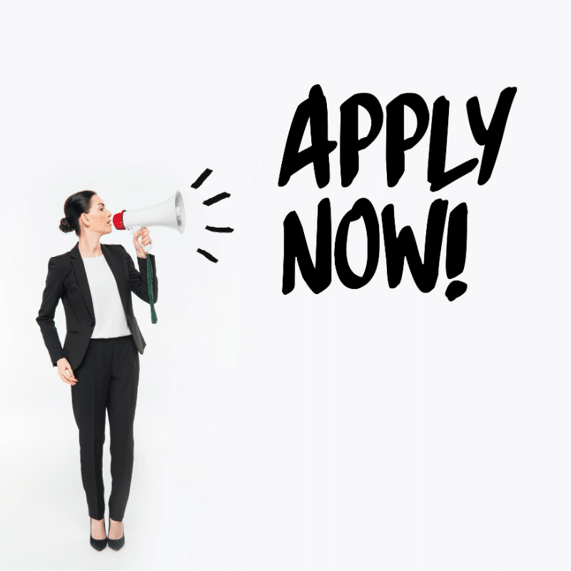 Lady wearing a black suit and white top shouting into a loud haler APPLY NOW!