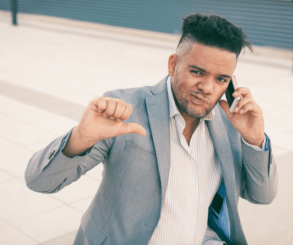 Man on the phone giving the thumbs down to a bad recruiter