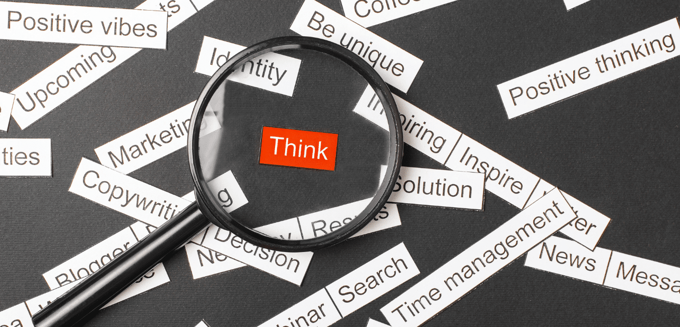 Word tiles on a black background with the word think highlighted in red, picked out by a magnifying glass
