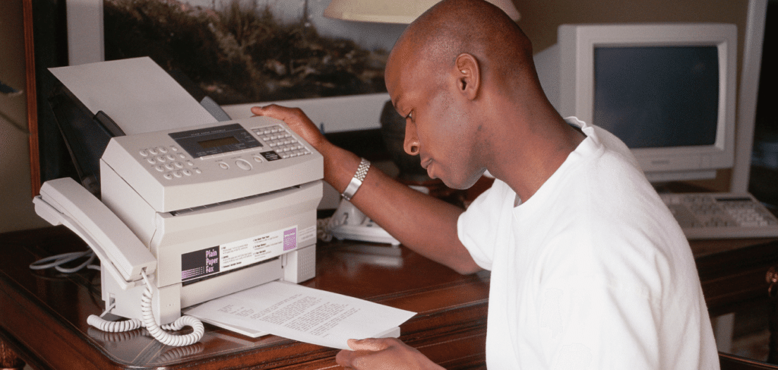 Man operating a fax machine, the ultimate recruitment technology in the 1990s