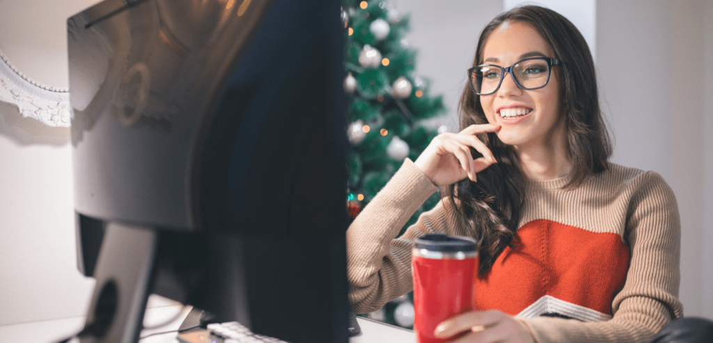 Lady smiling at her computer while drinking something festive