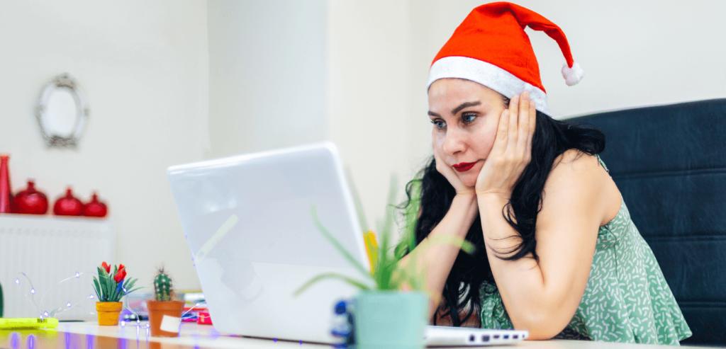 Young lady job hunting at Christmas at her laptop wearing a Santa's hat