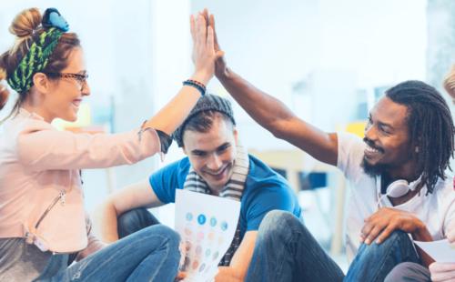 Digital agency team mates hi-five each other