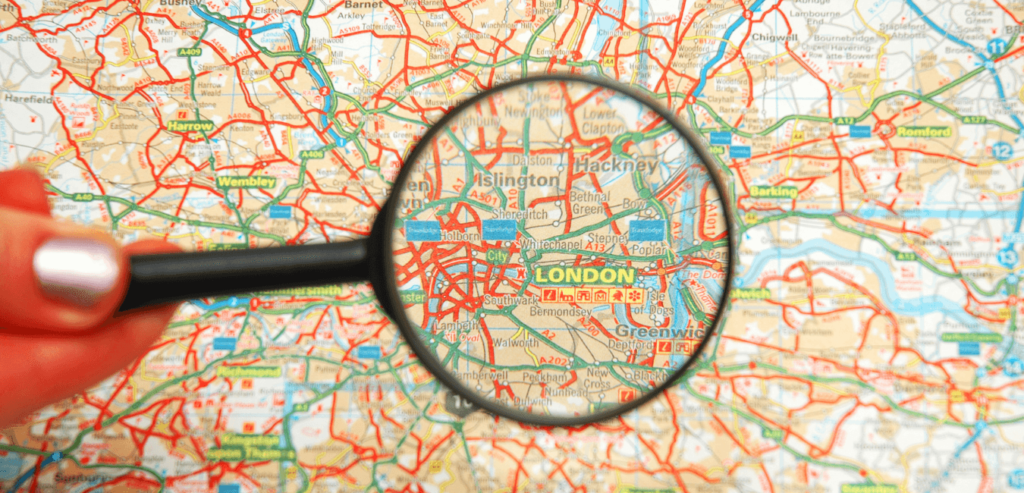 Hand holding a magnifying glass over London
