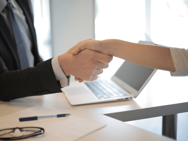 Interviewer successfully hiring tech talent shakes the hand of his new recruit