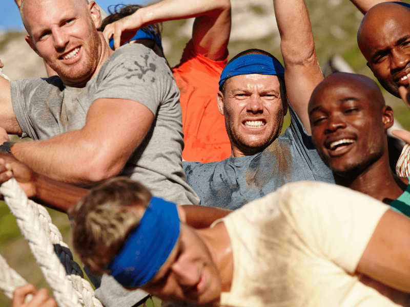 Lots of sweaty, muddy men on a physical bootcamp