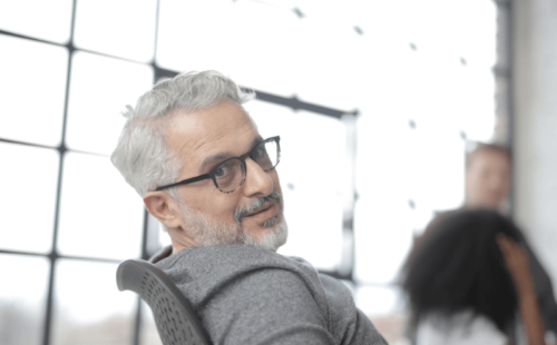 Employer looks right at the camera from his chair in front of a huge window