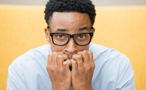 Employee suffering from return to work anxiety, slouched and biting his nails